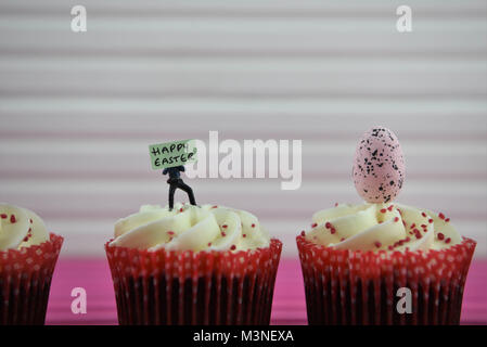 Easter time food cupcakes with miniature person figurine and sign board for happy Easter - Stock Photo