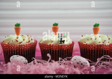 delicious Easter time cupcakes topped with miniature person figurine with sign board with I love Easter - Stock Photo