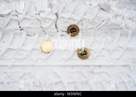 Copprito coins of gold bitcoin are lying on the snow. No one needed. In the winter on the road, traces of cars. - Stock Photo