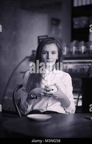 A girl in a cafe is drinking coffee. A woman is having breakfast - Stock Photo
