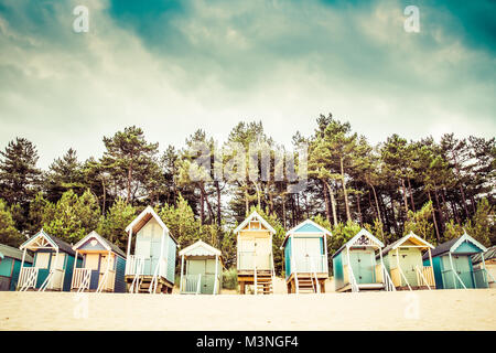 Colourful beach huts under the cover of a tree line on the sandy beach of Wells Next The Sea in Norfolk, UK. - Stock Photo