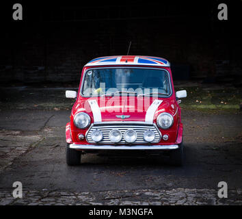 A front view of a classic, red Mini Cooper with a Union Jack flag on its roof and large, chrome headlights on a - Stock Photo