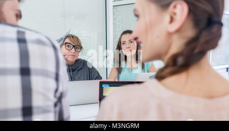 Side view of a creative female freelancer smiling to her co-worker, while making a call on the mobile phone at a - Stock Photo