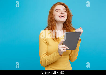 Close up Portrait young beautiful attractive redhair girl happy smiling on digital table with wining something. - Stock Photo