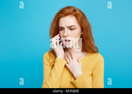 Portrait of a surprised confused woman in yellow casual calling mobile phone isolated over blue background - Stock Photo
