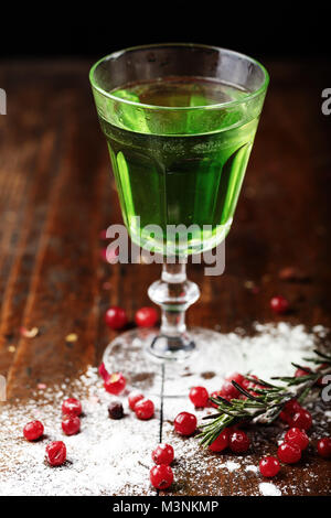 strong green alcoholic drink absinthe in a glass on the bar, beside scattered berries of cranberries - Stock Photo