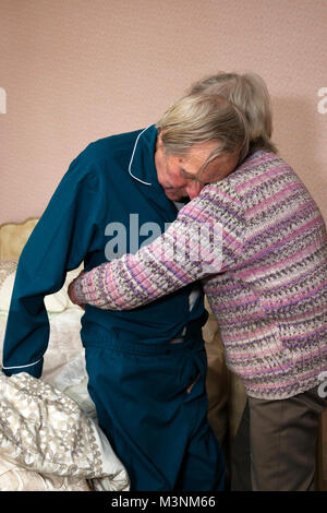 Sister helping elderly brother getting ready for bed - Stock Photo