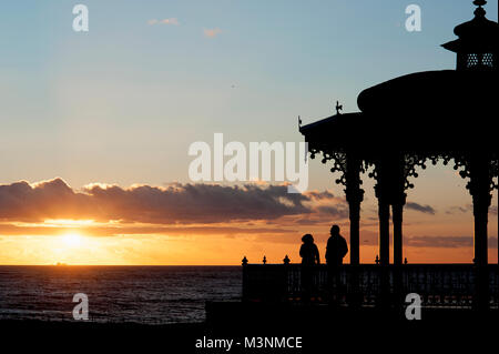 A couple enjoying a sunset view at the Bandstand on Hove's seafront  considered to be one of the finest examples - Stock Photo