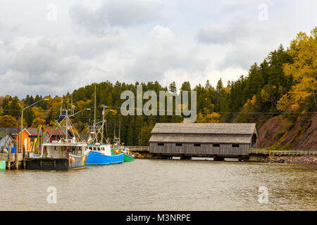 Beautiful autumn leaves, small commercial fishing village, old covered bridge, old colorful fishing boats docked - Stock Photo