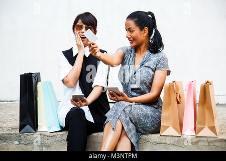 Smiling Female Ladies Shopping Concept with digital technology. Asian Buddy Female Shoppers happy shopping online - Stock Photo