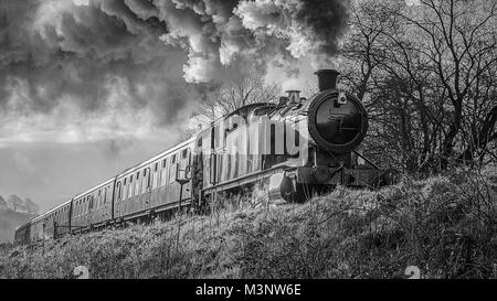 A black and white mono close up photograph of a steam train locomotive and carriages smoking and from a low angle - Stock Photo
