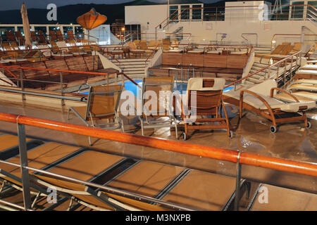 Recreation area at pool on cruise liner in evening - Stock Photo