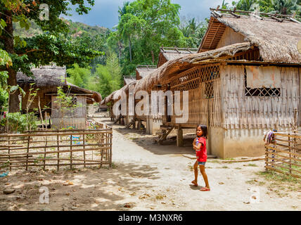 A young Filipino indigenous Mangyan girl walks to her home in the village of Talipanan with her water bottle. Oriental - Stock Photo