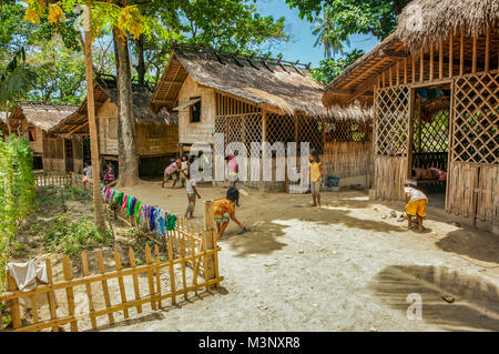 Young Mangyan preschool age children play improvised outdoor games together outside their bamboo nipa homes in Aninuan, - Stock Photo