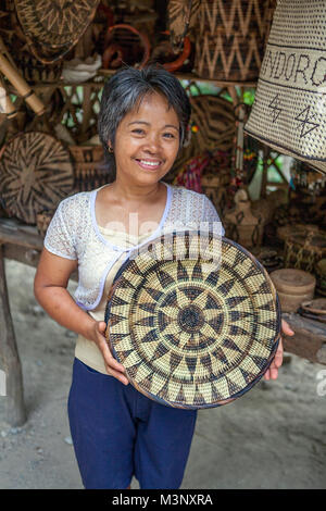 Aninuan, Oriental Mindoro, Philippines - A Mangyan craftswoman displays a nito platter she wove from rattan strips - Stock Photo