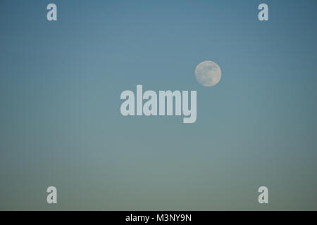 Full moon visible in the evening sky just before sunset - Stock Photo