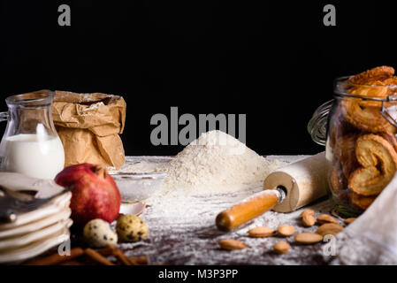 close-up view of delicious homemade cookies in glass bottle and ingredients for making dough on table top on black - Stock Photo