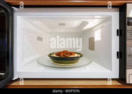 Kitchen home appliances cooking reheating plate bowl dish meal dinner of cooked spaghetti pasta with Bolognese tomato - Stock Photo