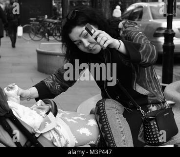 Mother taking a selfie with her baby in Oxford Street, Central London, England, UK, Credit: London Snapper - Stock Photo