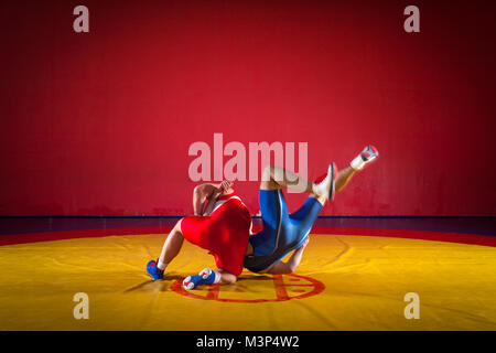Two strong wrestlers in blue and red wrestling tights are wrestlng and making a suplex wrestling on a yellow wrestling - Stock Photo