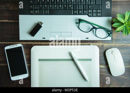 Top view of office stuff graphic design with pen mouse pad laptop wireless mouse and smart phone on wooden table.Concept - Stock Photo