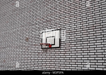 An old basketball hoop attached to a black and white brick wall in the small rural town of Oulainen in the Northern - Stock Photo