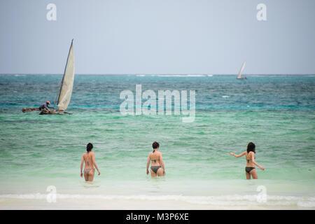 KIWENGWA, ZANZIBAR - DEC 29, 2017: tourists walking into the waters of Indian ocean, local fisherman on traditional - Stock Photo