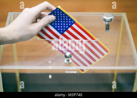 Man inserting Flag of United States of America into ballot box, voting and elections in United States of America. - Stock Photo