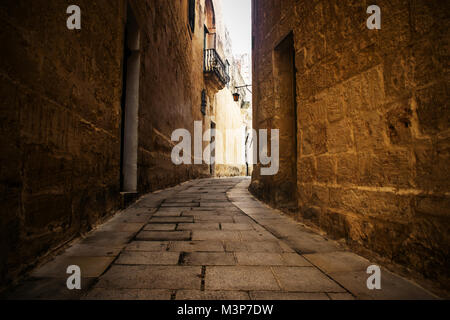 A typical narrow and historical road inlcuding cobblestone walls in Mdina, Malta. - Stock Photo