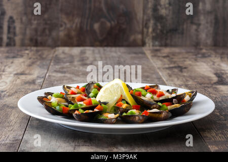 Steamed mussels with peppers and onion on wooden table - Stock Photo