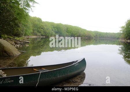 a green canoe on hothouse pond wakefeld south kingston rhode island USA - Stock Photo