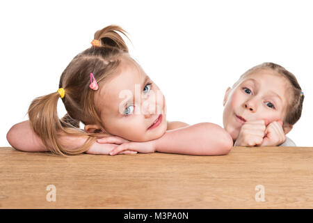 Portrait of two little girls sitting at the table and lined up on it isolated on white background - Stock Photo