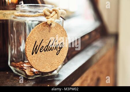Vintage retro glass jar with hemp rope tie wedding tag and few coins inside on wood counter concept of saving money - Stock Photo