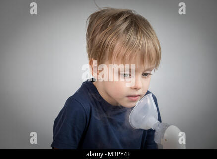 Little boy takeing inhalation for respiratory didease. - Stock Photo