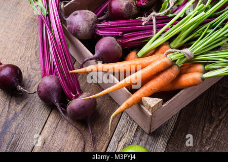 Crate with different fresh farm vegetables, organic  beetroots and  carrots on rustic wooden background - Stock Photo