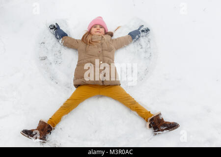 Image of girl lying on her back in snow at park - Stock Photo