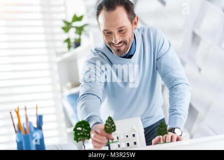Joyful architect constructing the model of a house - Stock Photo