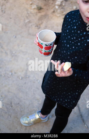 looking down at a five year old girl with red hair holding a chunk of apple and a white plastic cup with printed - Stock Photo