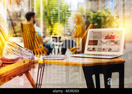 Modern laptop standing on the table while two people talking - Stock Photo