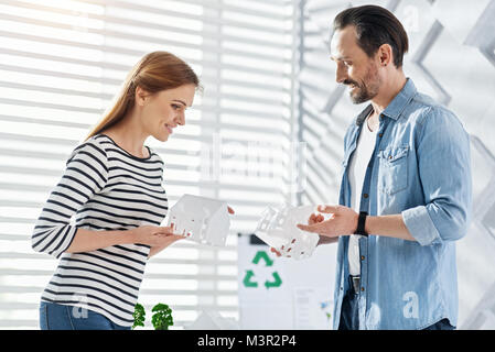 Cheerful landscape designers looking at their creations - Stock Photo