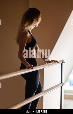 woman dancer posing near barre in ballet studio - Stock Photo