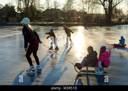 Young mother with children pulling a sled and skating on ice together in the Netherlands - Stock Photo