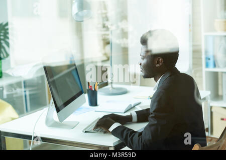 Successful African Businessman using PC - Stock Photo