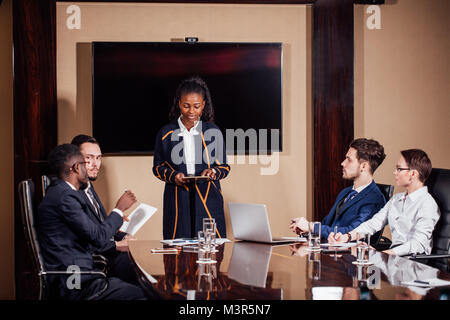 Businesswoman Leads Meeting Around Table Shot - Stock Photo