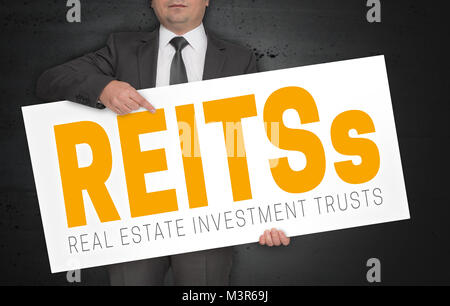 Reit poster is held by businessman. - Stock Photo