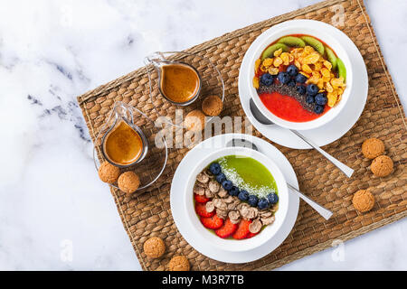 two bowls with different Smoothies from strawberries and kiwi, with Cereals for a healthy Breakfast and berries, - Stock Photo