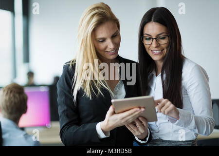 Portrait of two attractive businesswomen using tablet in office - Stock Photo