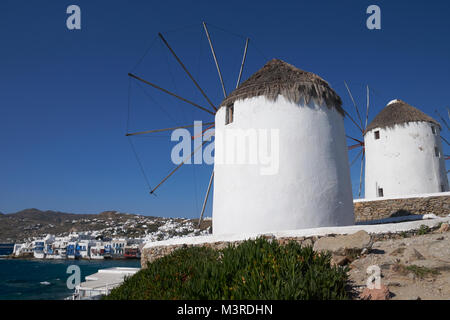 Iconic windmills overlooking the town of Mykonos (Chora), Cyclades Islands, Aegean Sea, Greece. - Stock Photo