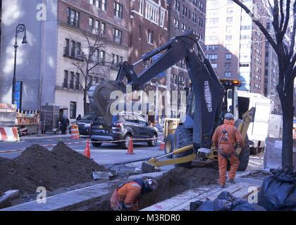 Men dig deep under East 86th Street to do infrastructure repair work. Manhattan, NYC - Stock Photo