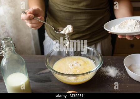 Baking pancakes in rural kitchen - Stock Photo